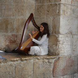 Erfreulicher Gruß für Auge und Ohr; Harfenspielerin an altem Stadtor